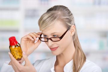 apothekerin schaut prüfend auf medikament