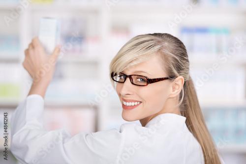 apothekerin nimmt ein medikament aus dem regal