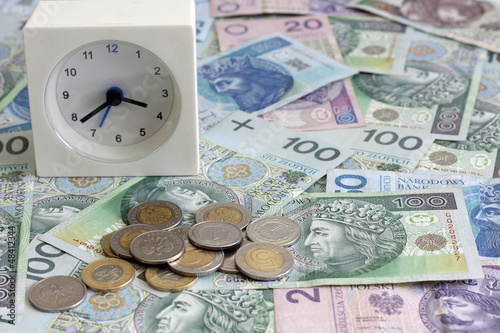 Time is money concept with polish coins and banknotes