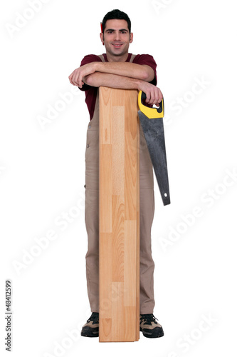 Worker holding a saw and leaning against a wooden plank