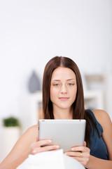 junge frau schaut auf tablet-pc