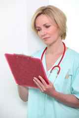A female doctor taking notes on a clipboard.