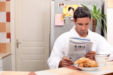 Man reading his newspaper over breakfast