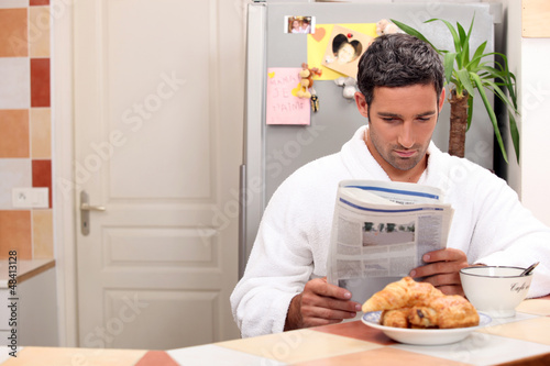 Man reading his newspaper over breakfast