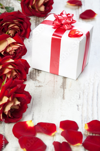 gift box on a white board with red roses