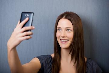junge frau fotografiert sich mit ihrem smartphone