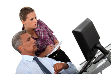 Businessman and his assistant looking at a computer