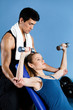 Coach helps woman to exercise with dumbbells in training gym