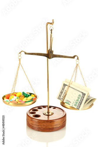 Pills and money in scales isolated on white