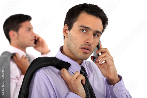 two young businessmen talking on their cells