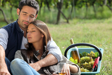 Couple sat by basket full of grapes