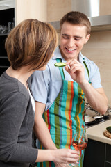 Man in apron feeds his wife with vegetables