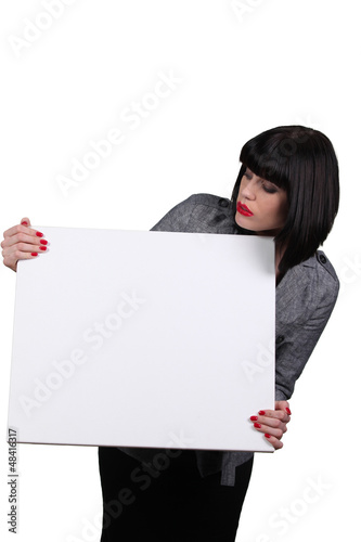 Young woman holding white panel
