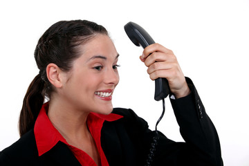 Brunette businesswoman receiving positive phone call