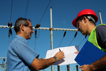 Engineer Showing Blueprint to Worker