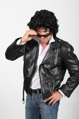 Man in a silly black wig and biker jacket