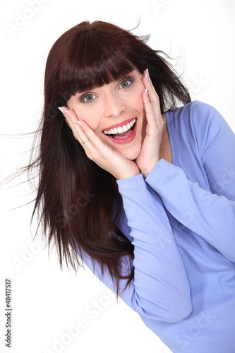 Delighted woman with her hands to her face