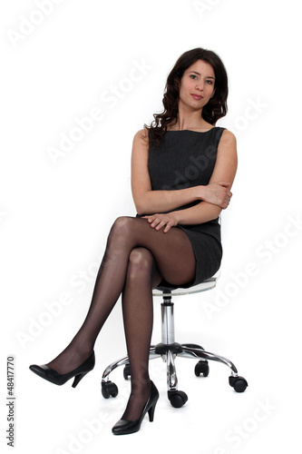 Young businesswoman sitting on an armchair, studio shot