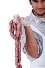 A butcher holding sausages.