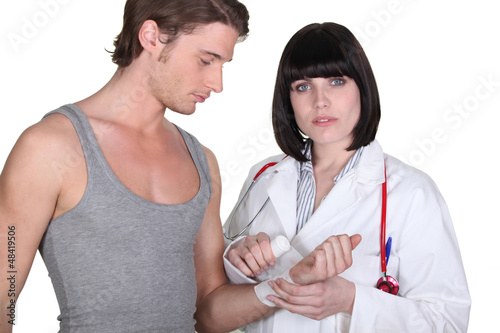 Doctor wrapping gauze around a patient's wrist