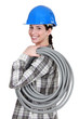 Tradeswoman carrying corrugated tubing