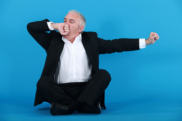 A mature businessman yawning.