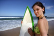 Brunette stood on beach with surfboard