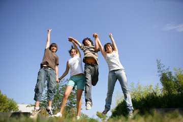 Group of teenagers holding hands and jumping in the air