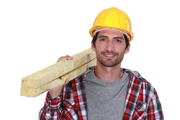 Carpenter carrying planks of wood over shoulder