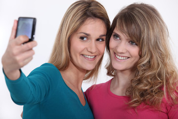 Two girls taking a picture of themselves.