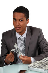Young businessman counting money