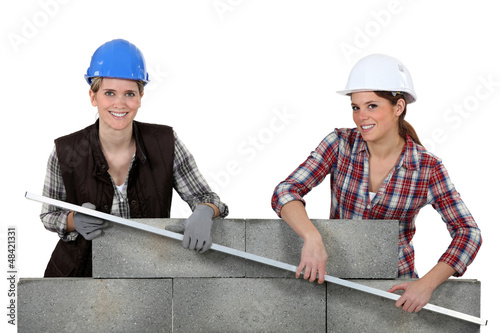Female construction workers lifting a bar