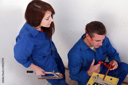 Plumber cutting copper pipe while his female apprentice watches