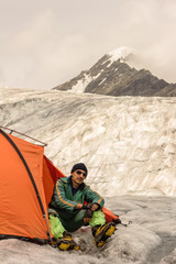 The rock-climber in tent looks to tops mountains