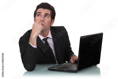 Daydreaming businessman sat at his desk