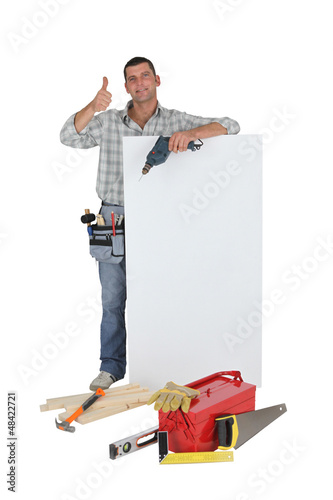 Approving tradesman posing with a blank sign and his tools
