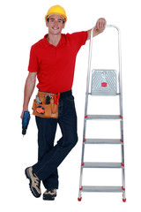 Worker with a stepladder and cordless drill