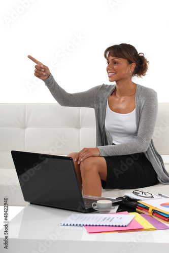 Businesswoman sat on sofa pointing