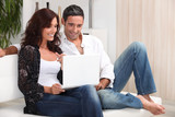 Couple on a sofa with a laptop