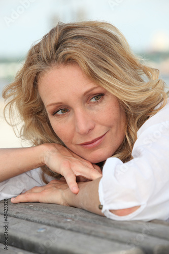 Thoughtful woman resting her head on the back of a bench