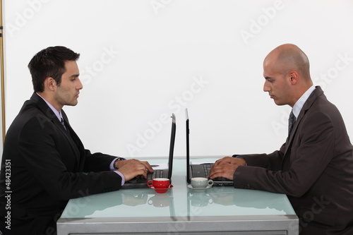 Two businessmen with coffee and laptops