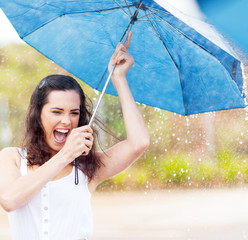 playful young woman holding umbrella in the rain