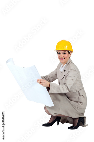 Female architect kneeling with blueprints