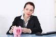 Attractive businesswoman checking piggy bank