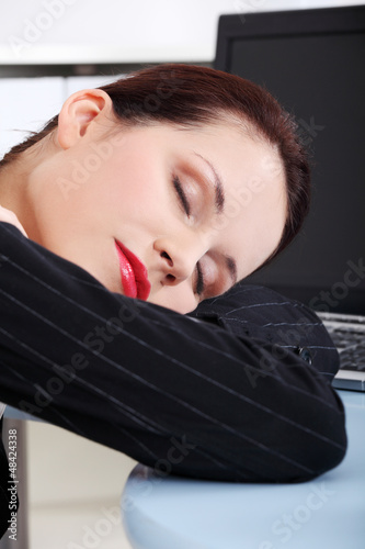Tired businesswoman sleeping at the desk.