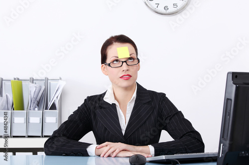 Businesswoman at office with post it on her forehead.