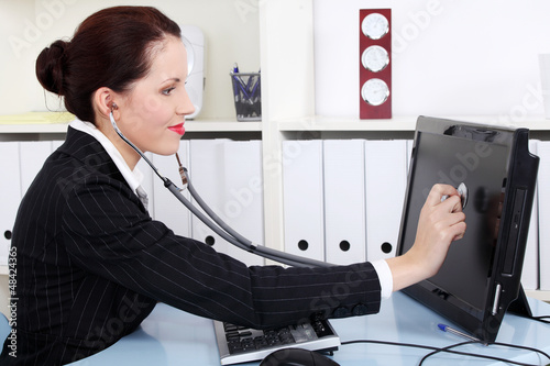Businesswoman with sthetoscope checking pc