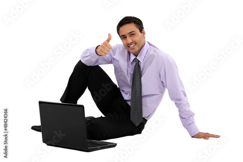 businessman sitting on the floor with his laptop