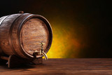 Old oak barrel on a wooden table. Behind blurred dark background