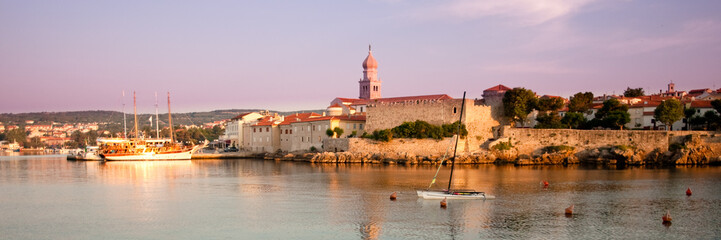 Panoramic view of Krk port and city walls from the sea with morn
